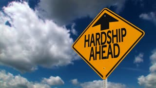 A road sign warns of hardship ahead.