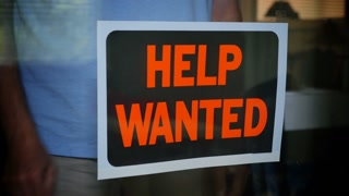 A shop owner places a help wanted sign in the window.