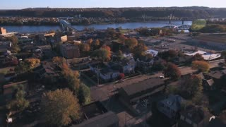 A slowly moving backward aerial shot of a typical Western Pennsylvania small town in the Autumn. Ohio River in distance. Pittsburgh suburb.