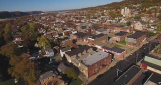 A slowly moving backward aerial shot of a typical Western Pennsylvania small town in the Autumn. Pittsburgh suburb.