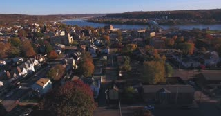 A slowly moving forward aerial shot of a typical Western Pennsylvania small town in the Autumn. Ohio River in distance. Pittsburgh suburb.