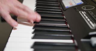 A slowly tracking dolly shot of a person playing a piano or electric keyboard.