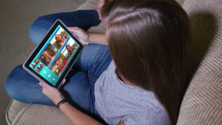A teenager video chats on her tablet PC.