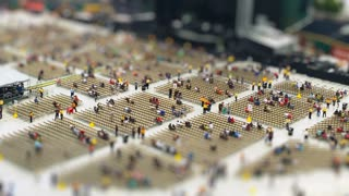 A time lapse tilt shift view of fans crowding into their seats on the floor of a concert venue.