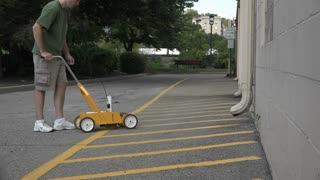 A timelapse shot of a man painting new yellow lines in a parking lot.