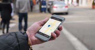 A woman uses a smartphone to observe ride sharing traffic patterns on an interactive map in a fictional city.