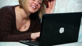 A woman uses her laptop in the bedroom.