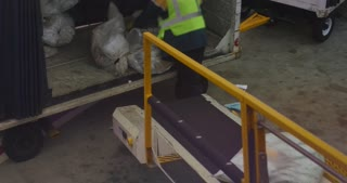 A worker loads bags of US Postal Service mail onto a commercial jet at an airport.