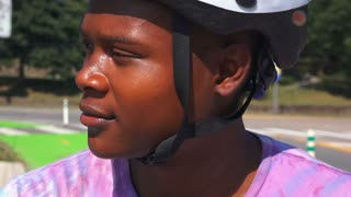 A young African American teenager in a bike helmet looks at the camera and smiles.  Shot at 60fps.