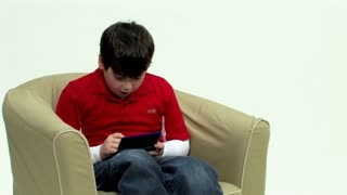 A young boy plays a hand-held video game.