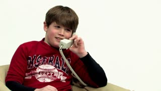 A young boy talks on the telephone.