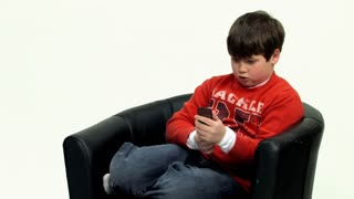 A young boy texts on his mobile cell phone.