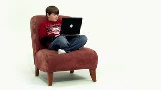 A young boy uses his laptop computer.