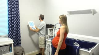 A young expecting couple clean and prepare their new nursery before the birth of their new baby.