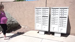 A young expecting mother walks outside to get her mail from the communal mailbox in a typical Arizona neighborhood housing plan.