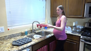 A young expecting woman works by the kitchen sink.