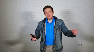 A young man dances playfully in front of a white brick wall with his cellular telephone.