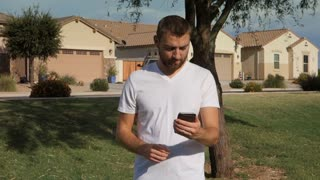 A young man plays an augmented reality game on a smartphone in a typical Arizona neighborhood.