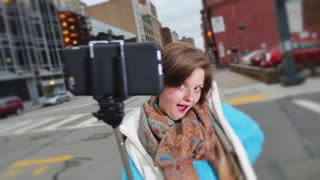 A young woman playfully poses outside with a selfie stick.