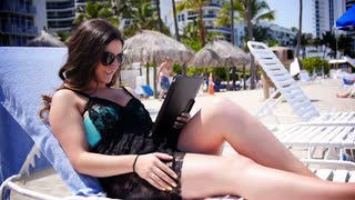 A Young Woman Reading an eBook at the Beach