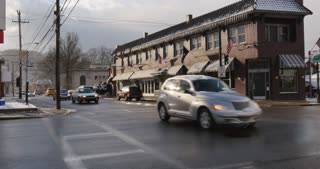AMBRIDGE, PA - Circa February, 2017 - A wintertime establishing shot of traffic passing by a corner bar and restaurant.