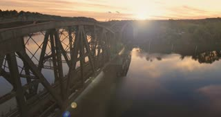 An aerial establishing shot of a railroad bridge in a Western Pennsylvania river valley at sunset. Pittsburgh suburb.
