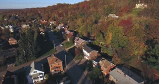 An aerial view looking down on a small Western Pennsylvania town and residential neighborhood on an Autumn evening. Pittsburgh suburb.