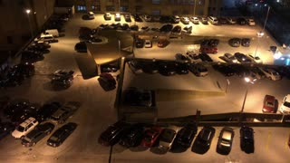 An aerial view of a crowded parking lot at night.