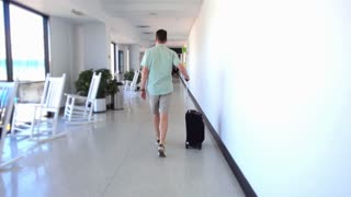 An airline passenger walks down an airport hallway pulling his wheeled suitcase.