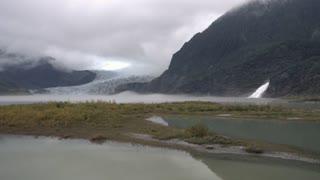 An establishing wide shot of Mendenhall Glacier near Juneau, Alaska on a foggy day.