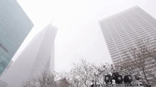 An exterior establishing shot of tall buildings in the winter in Manhattan.