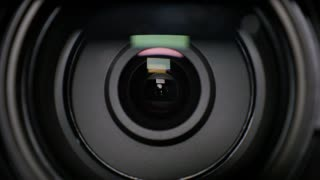 An extreme closeup of a zooming camera lens.