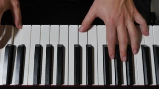 An overhead slowly tracking dolly shot of a person playing a piano or electric keyboard.