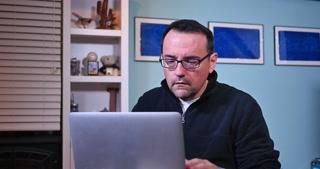 An upset man at his laptop.