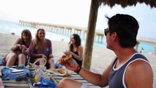 Young Millennials Having a Beach Pizza Party