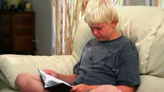Young Boy Reads a Book on the Sofa