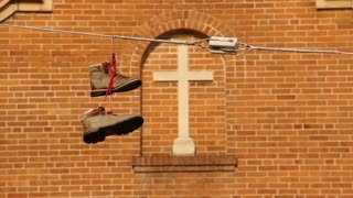 Boots on a Power Line in Front of Church