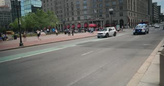 BOSTON, MA - Circa June, 2016 - A Boston police car races past pedestrians near Copley Square.