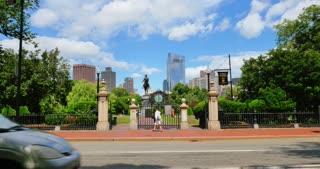 BOSTON, MA - Circa June, 2016 - A summer daytime establishing shot of traffic on Arlington Street passing the entrance to Boston Public Garden.