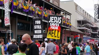 NEW ORLEANS, LA - Circa February, 2014: Protestors walk the streets of the French Quarter while onlookers on above balconies throw beads to willing participants below.