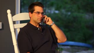 Man Talks on Telephone Outside on Porch