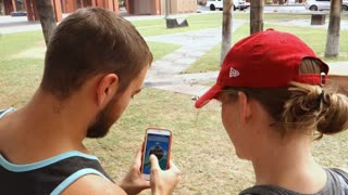 CHANDLER, AZ - Circa July, 2016 - Two millennials play the popular smartphone game, Pokémon Go in a public park.