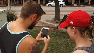 CHANDLER, AZ - Circa July, 2016 - Two millennials play the popular smartphone game, Pokémon Go in a public park.