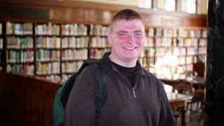 Confident Young Man Student in Library Smiles to Camera