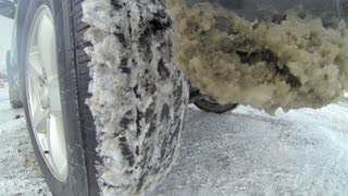 Detail of a rear tire while driving in the snow.