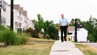 Door-to-Door Salesman Walking in Sidewalk in Neighborhood