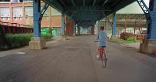 Following a biker riding under the 31st Street Bridge in Pittsburgh's industrial district.