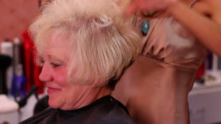 Hair Salon Stylist Attends to Client in Chair