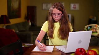 Young Girl Does homework at dining Room Table