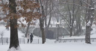 Joggers run on the pathways of Manhattan's Central Park during a December winter snowstorm.